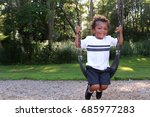 a young black boy is swinging... | Shutterstock . vector #685977283