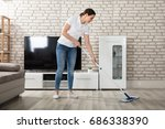 happy young woman cleaning the... | Shutterstock . vector #686338390