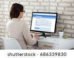 Small photo of Rear View Of A Businesswoman Filling Survey Form On Computer In Office