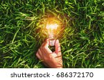 Hand hold light bulb on grass ...