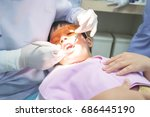 Small photo of Real event photo, Cute little asian boy wearing glasses sitting in the dental chair and open him mouth during oral checkup with dentist To fill the tooth decay.