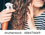 woman applying spray on curly... | Shutterstock . vector #686476669