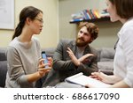Small photo of Portrait of young Asian woman accusing her husband of adultery showing text messages on mobile phone in couples counseling session