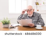 Small photo of Shocked senior man looking at bills in disbelief, holding his glasses on forehead, copy space