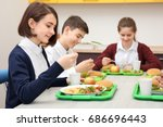 children sitting at table in... | Shutterstock . vector #686696443