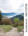 Small photo of Trekking way to Harder Kulm with Thun lake and mountain range as background. Selective focus on mountain range.