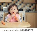 baby girl eating vegetable at... | Shutterstock . vector #686828029