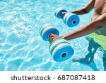 Small photo of Hands of an unknown black guy holding dumbbells for aqua aerobics standing in the swimming pool on warm summer day