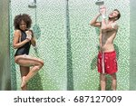Small photo of Happy youthful couple taking douche on public beach