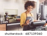 cheerful young woman cashier is ... | Shutterstock . vector #687139360