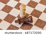 Small photo of chess game. abstract composition of chess figures. isolated on desk background. one by one. white king win black king. utter defeat.