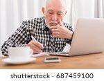mature man using laptop and... | Shutterstock . vector #687459100