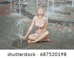 Small photo of Woman sits in a fountain, she is all wet.