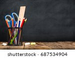 Desk Of Student, Pencils In Metal Holder On Blackboard Background - stock photo