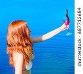 Small photo of Red hair young woman in swimsuit rest near blue water with glass of red wine. The wine is poured from the glass. The concept of disintegration and getting rid of unnecessary and old