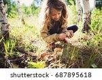 happy child girl picking wild... | Shutterstock . vector #687895618
