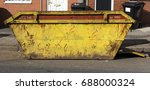 Small photo of Large rusted yellow skip/dumpster