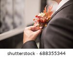groom attach flowers to the... | Shutterstock . vector #688355344