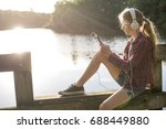 girl sitting at the lake with...   Shutterstock . vector #688449880