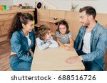 Small photo of beautiful young family playing guess sticker in cafe