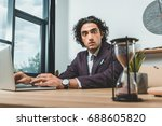 Stock photo selective focus of businessman working on laptop and looking at sand clock while struggling to meet 688605820