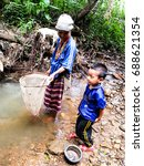 Small photo of MAEHONGSON,THAILAND -June 15,2014:The remote village and Deep in the summer, most people, including children, are out looking for food near the house.Which is a food source that is readily available.
