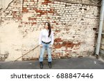 woman by the brick wall | Shutterstock . vector #688847446