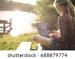 girl using her laptop outside... | Shutterstock . vector #688879774