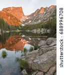 Small photo of The first reddish light of alpenglow hits Hallett Peak, reflected in Dream Lake in Rocky Mountain National Park, Colorado