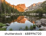 The first reddish light of alpenglow hits Hallett Peak, reflected in Dream Lake in Rocky Mountain National Park, Colorado