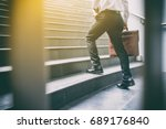Small photo of Businessman walking up the stairs hastily. In his hand is a brown leather briefcase. with flare light.