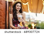 Small photo of People, food, rest and lifestyle concept. Brunette woman with long hair, wearing summer dress and hat, drinking takeaway coffee and eatting croissant while sitting at outdoor cafe, resting alone