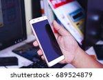 hand holding smartphone in... | Shutterstock . vector #689524879