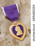 Small photo of Purple Heart Medal Laying on Military Fatigues