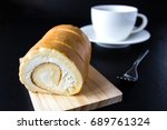 swiss roll and coffee on wood... | Shutterstock . vector #689761324