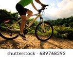 Woman cyclist cycling mountain bike on trail - stock photo