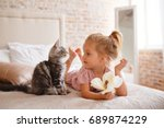 Stock photo pets morning comfort rest and people concept happy little girl with cat in bed at home 689874229