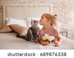 Stock photo little girl relaxing on the bed with her kitten child is kissing a cat 689876338