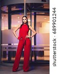 Small photo of Young posh lady wearing appealing red costumes standing ahead glass door. Bright illumination coming from inside the door. Lady posing like a model looking bold with hands placed on hip.