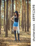 Small photo of Stylish brunette woman walk into forest have a grace and charisma. Young lady in fedora black hat and interesting accessorize