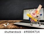 School Desk, Pencils And Various Supplies In Metal Shopping Holder On Laptop With Blackboard Background - stock photo