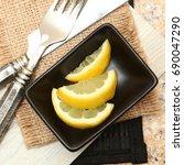 lemon slices in small black... | Shutterstock . vector #690047290