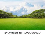 Small photo of Green grass green trees in beautiful park white Cloud blue sky in noon. Beautiful park scene in public park with green grass field, green tree plant and a party cloudy blue sky