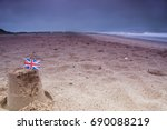 Small photo of A abandoned sandcastle with a Union Jack flag in bad weather at the height of summer at Dawlish, Devon, England, UK