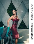 Small photo of Stylish lady standing confidently inside elegant room. Woman having shining sleek black hair dressed in tight leather one piece and accessories smiling and posing sidewise with one leg bent.