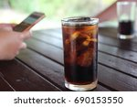 black water in glass on wood...   Shutterstock . vector #690153550