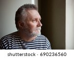 Small photo of Serious adult man with grey hair looking into the window