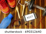 Small photo of Fitness, healthy and active lifestyles concept. Dumbbells, sport shoes, smart phone with earphone, skipping rope and water bottle on wooden gym floor with word HIIT (High Intensity Interval Training)