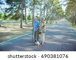 Stock photo senior couple in the park with dog on a summer day 690381076