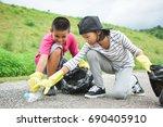 children hands in yellow gloves ...   Shutterstock . vector #690405910